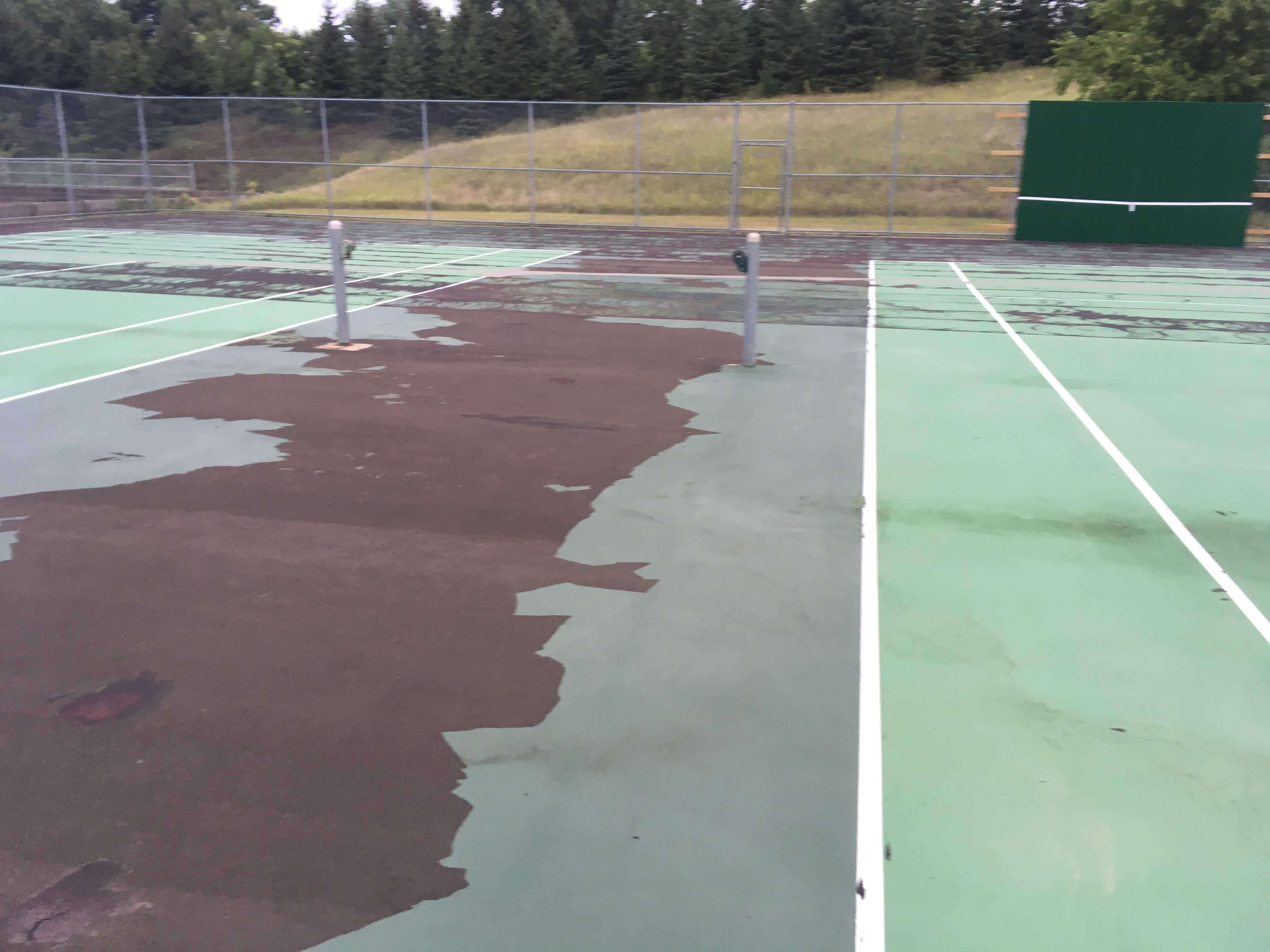 Tennis court BEFORE completed resurfacing and crack repair by C & H Sport Surfaces, Inc