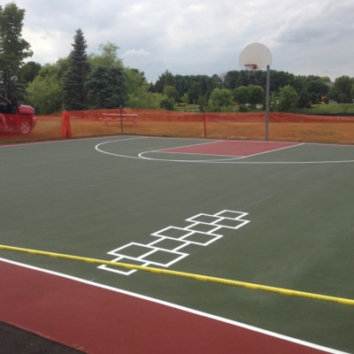 Green and red basketball court with hopscotch