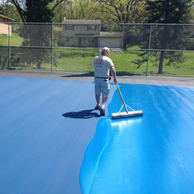 Adding blue to the tennis court surface during the resurfacing stage