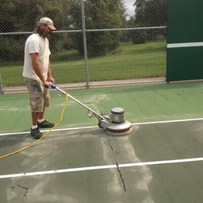 Sanding tennis court before applying paint
